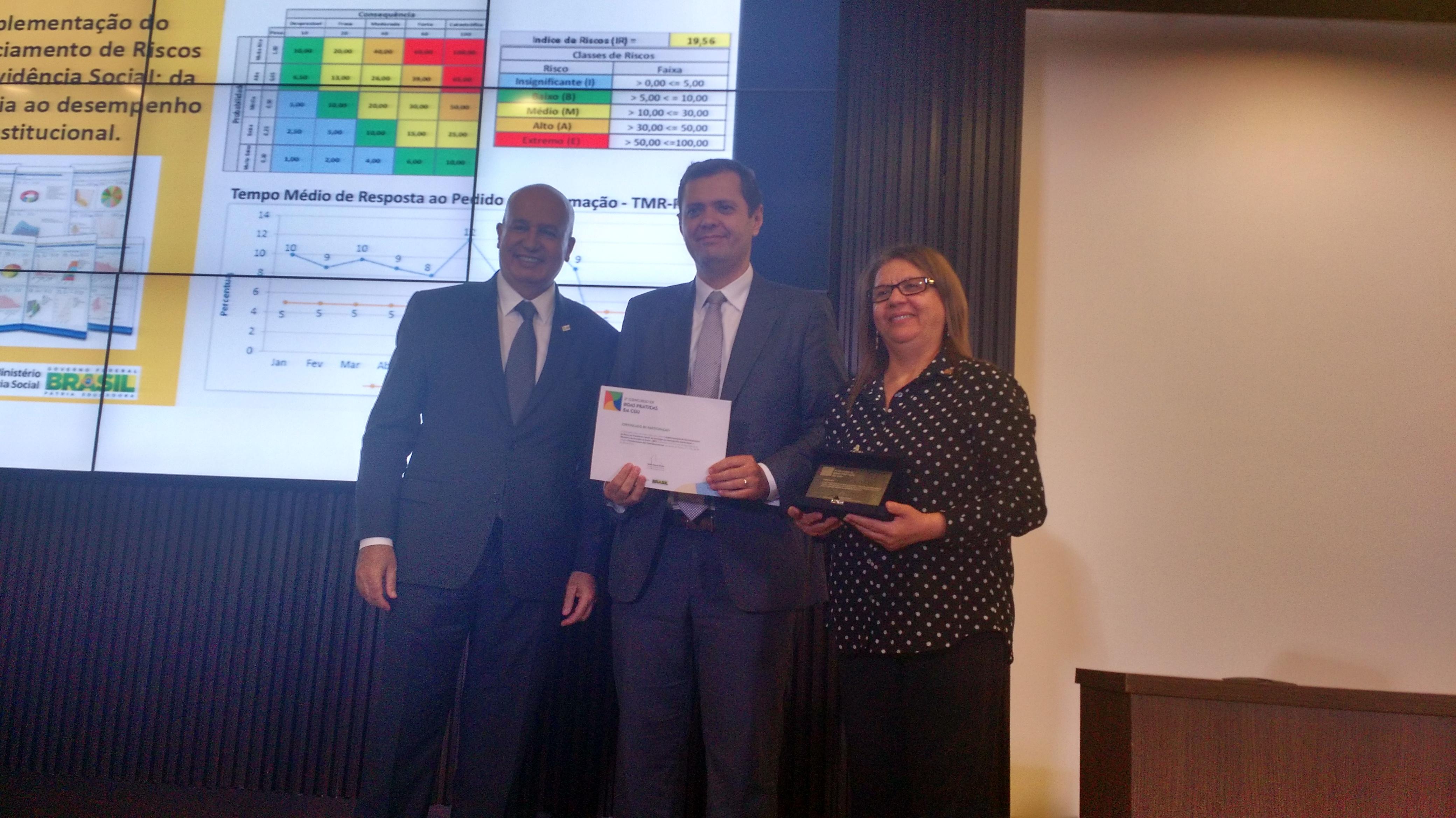 O ministro-chefe da CGU, Valdir Simão, entrega o prêmio para o secretário-executivo do MTPS, Cláudio Puty, e para a assessora do MTPS, Nicir Chaves. Foto: João Victor Bezerra.
